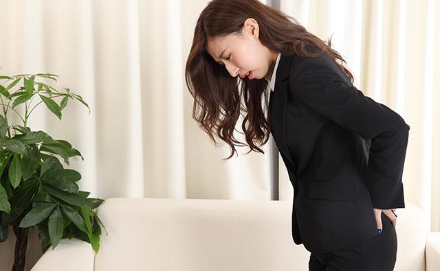 腰痛で仕事に支障が出ているビジネススーツの女性